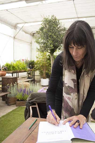 Camilla mentre autografa una copia del suo libro al vivaio Sisaflor di Forlì